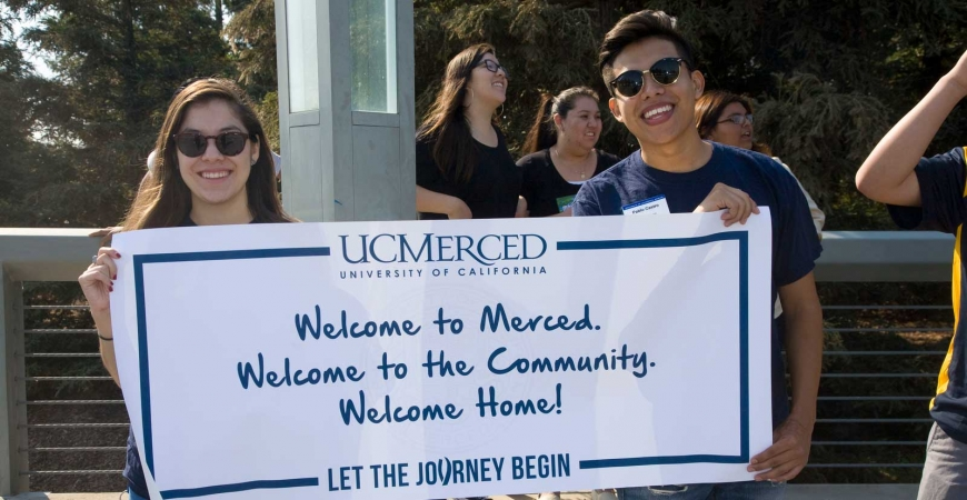 Two students hold a sign that reads: Welcome to UC Merced. Welcome to the Community. Welcome Home!