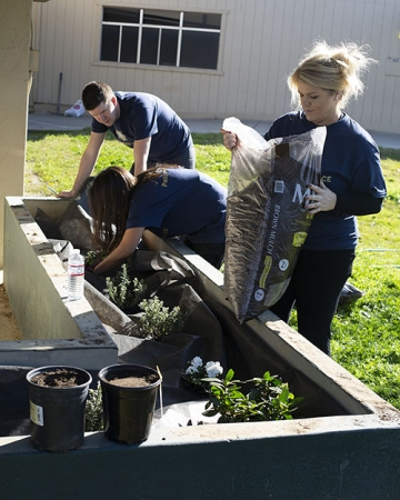 UC Merced Police Sgt. Kari Gomes prepares to spread soil among freshly planted flowers at the local elementary school.