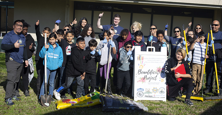 UC Merced Police Department officers, student mentors and Margaret Sheehy Elementary School students gather for a group photo during their beautification project.