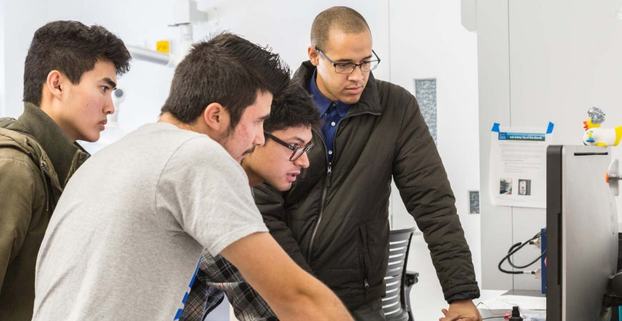 Four male students huddle around a computer as they work.