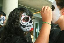student painting another's student face for chicano history month